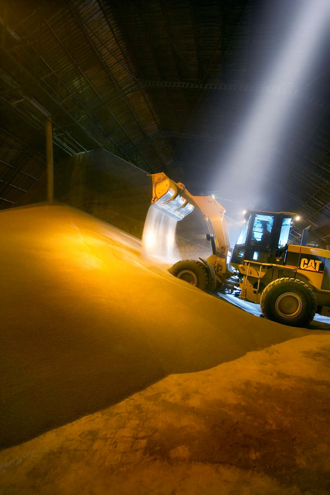 Loader handling ammonium nitrate - yellow metal photography by professional photographer