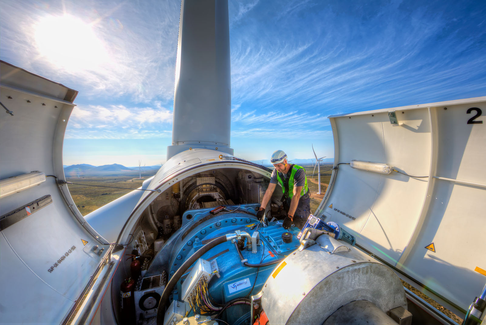Technician performs maintenance on a wind turbine generator part of industrial photography portfolio