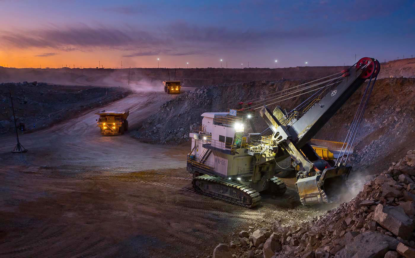 Hydraulic shovel and haul trucks at work in an open cast mine - mining photographer portfolio