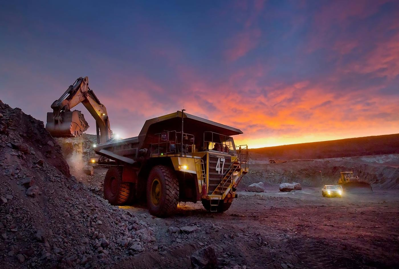 Hydraulic shovel and haul truck at iron ore mine at sunset - Mining equipment photo portfolio