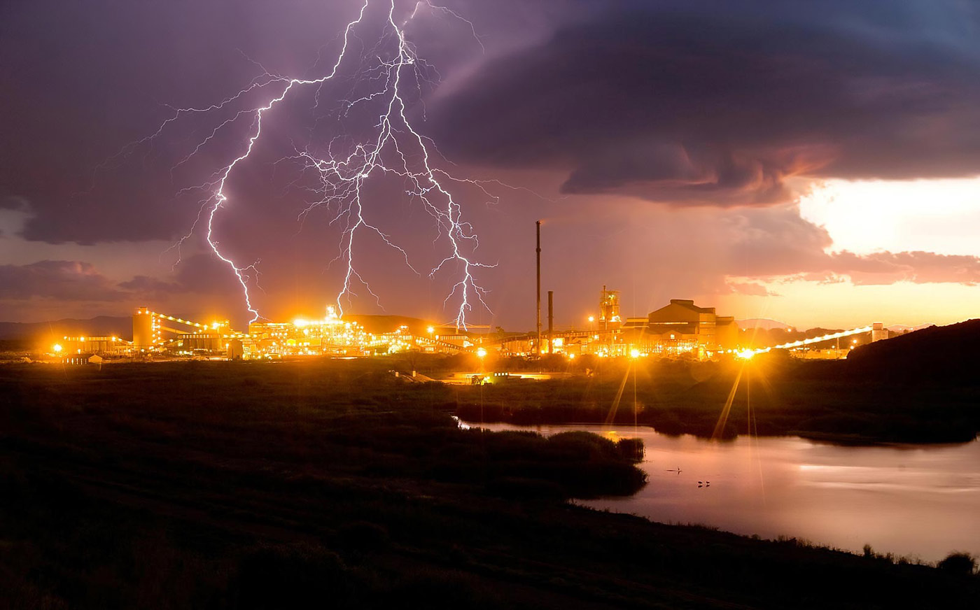 Lightning striking over smelter complex, industrial photography by Planet KB