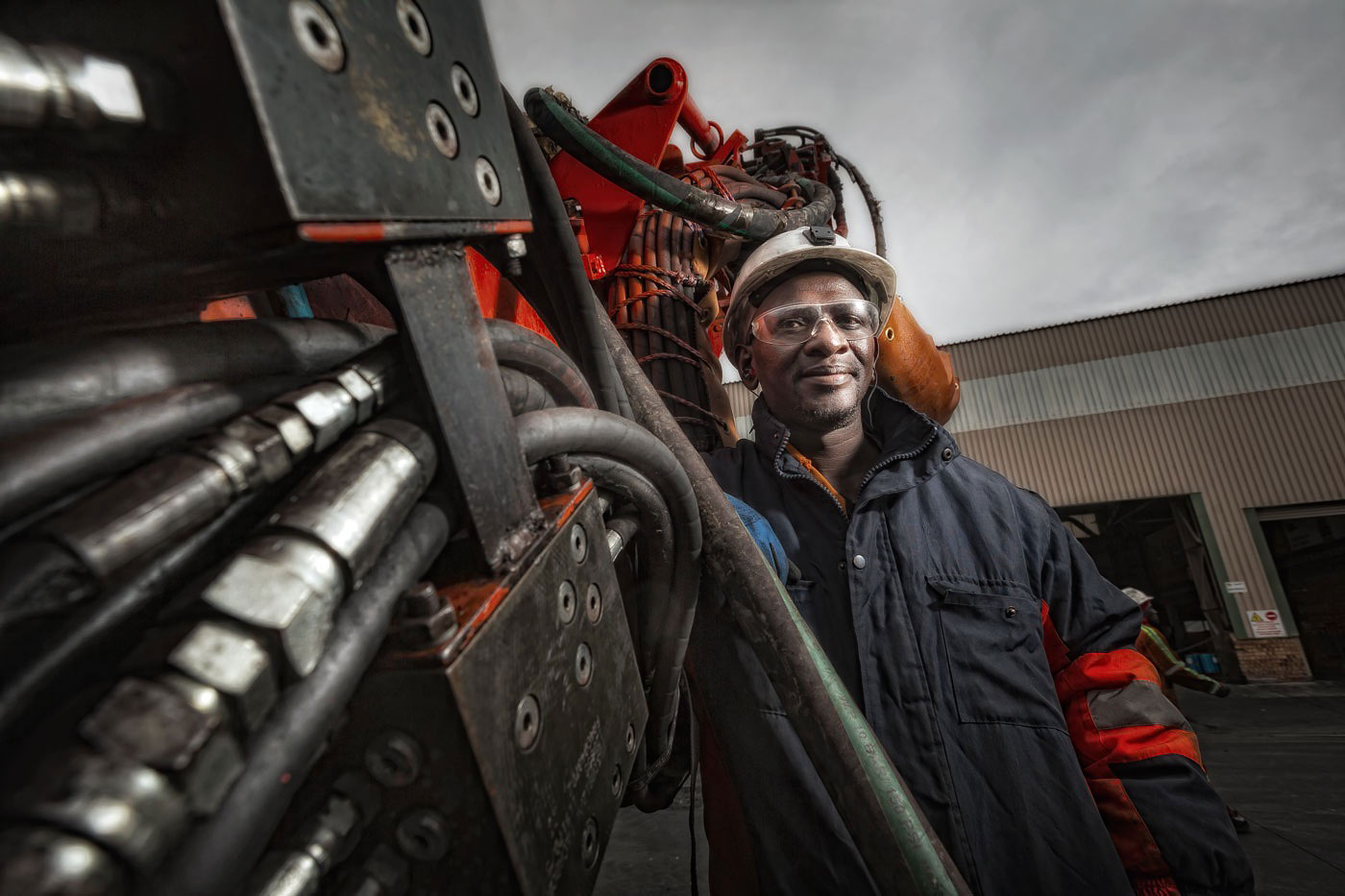 Mechanic with drill rig at mine workshop - mining equipment photography