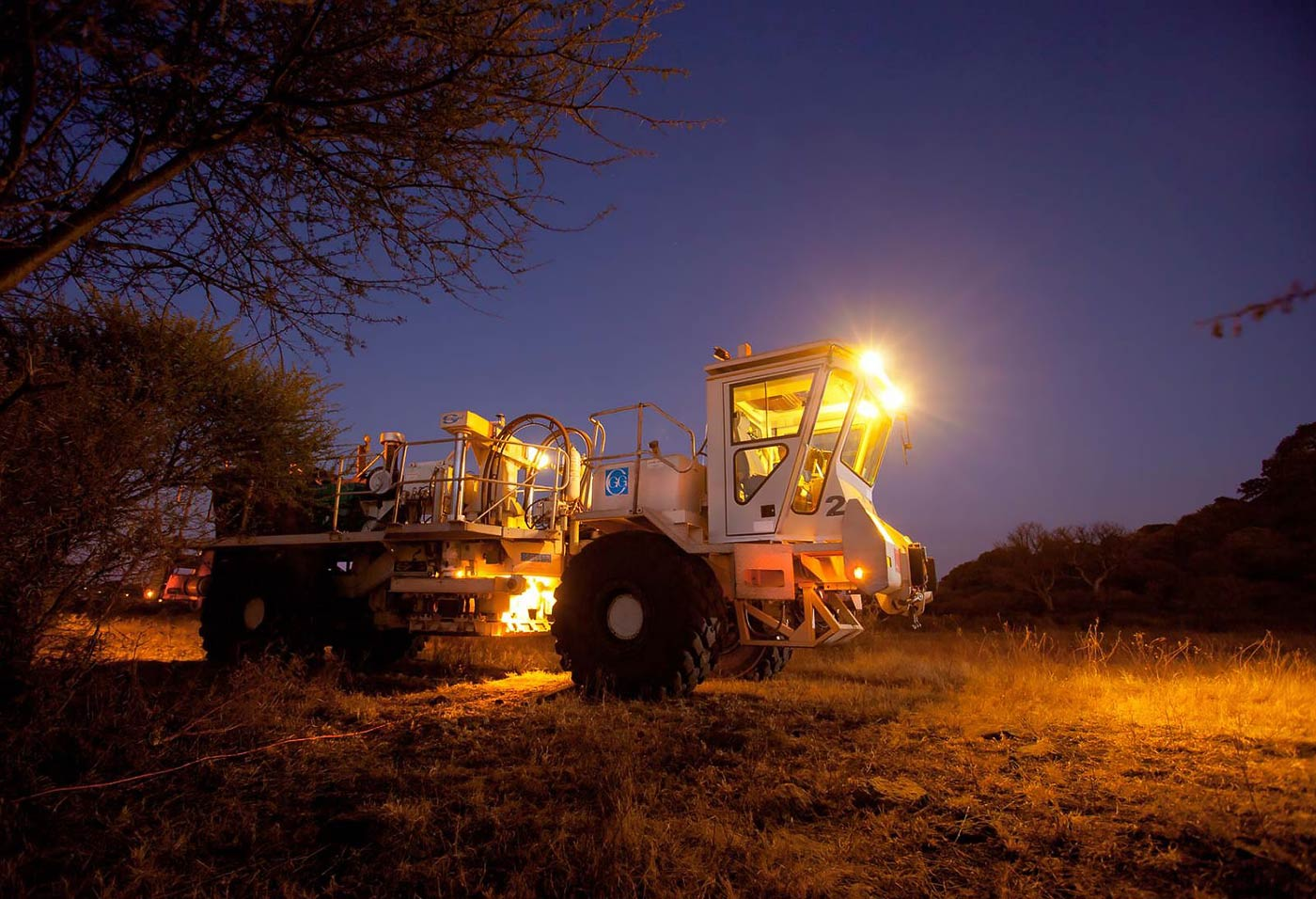 Seismic exploration thumper truck in the field at night - mining equipment photograph