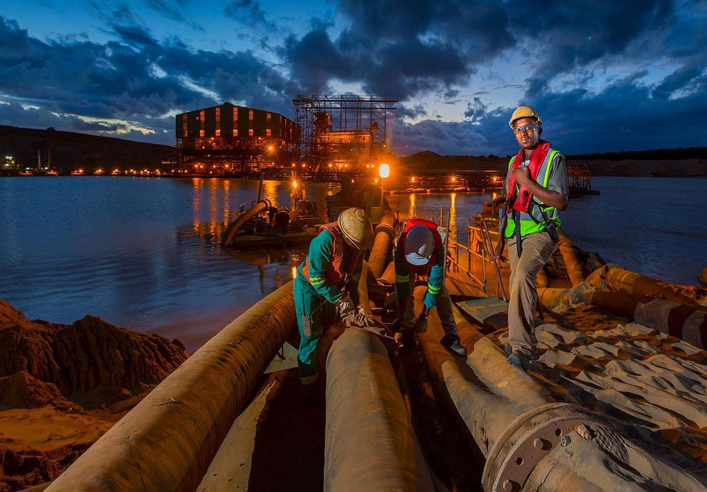 Workers repair slurry pipelines - mining photography by Planet KB