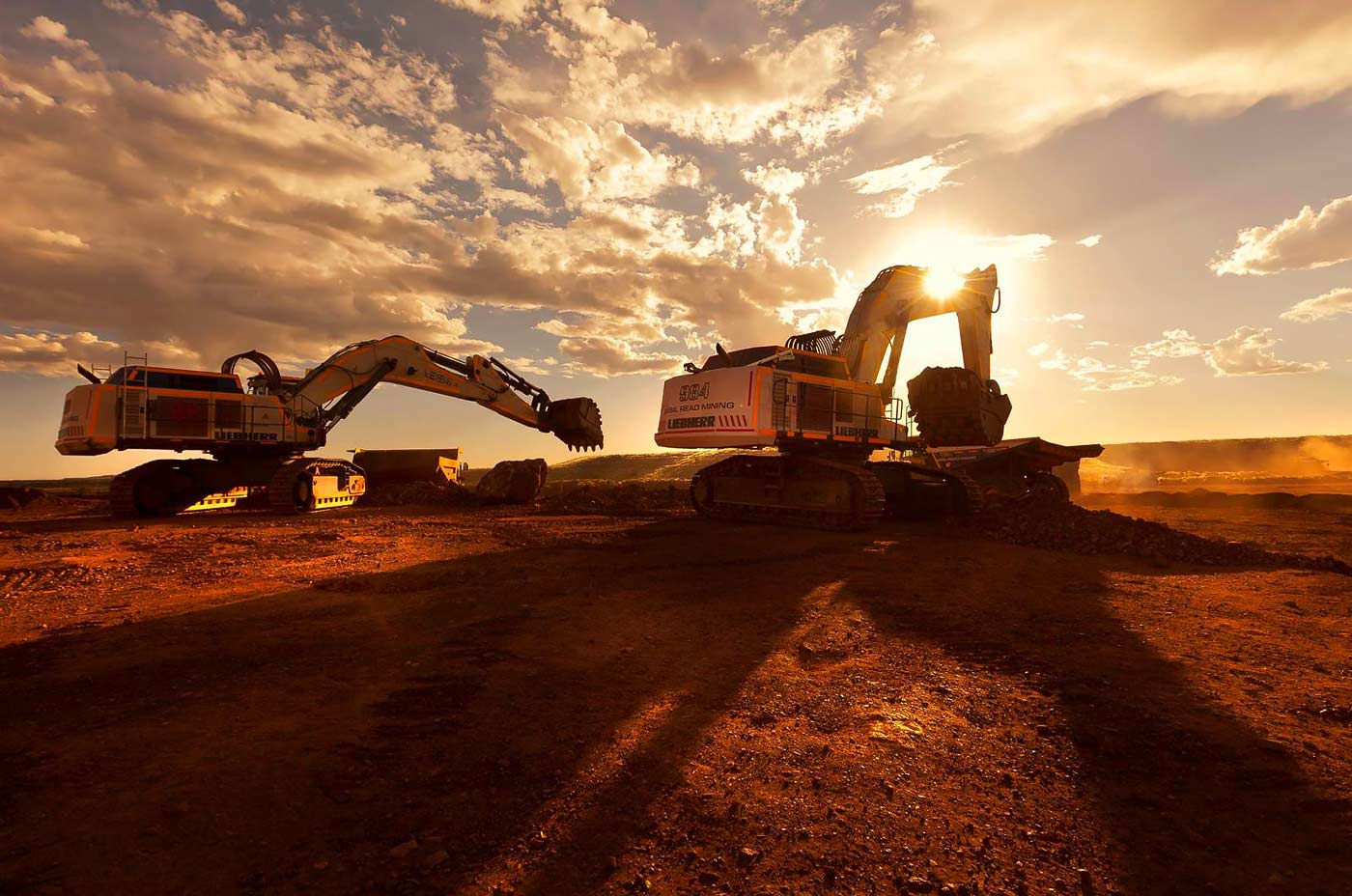 Excavators at work at open pit iron ore mine - mining machinery photography