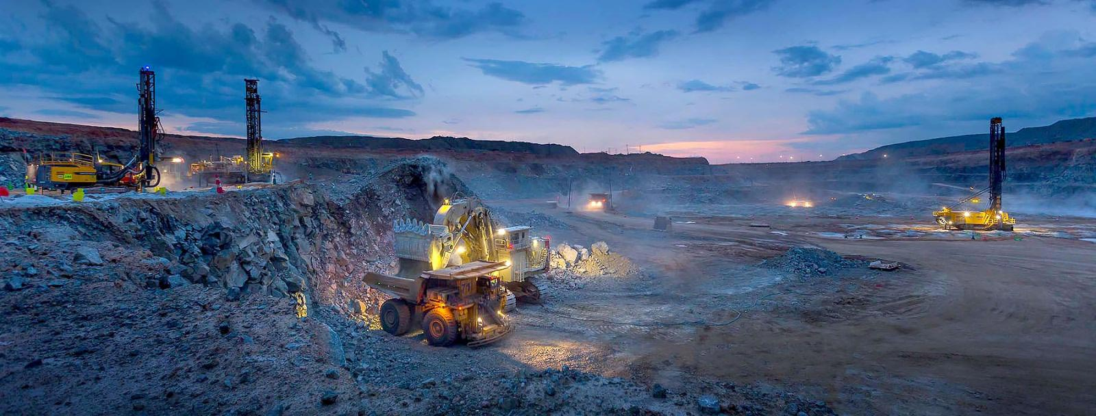 Drilling load and haul operations at open pit mine at sunset