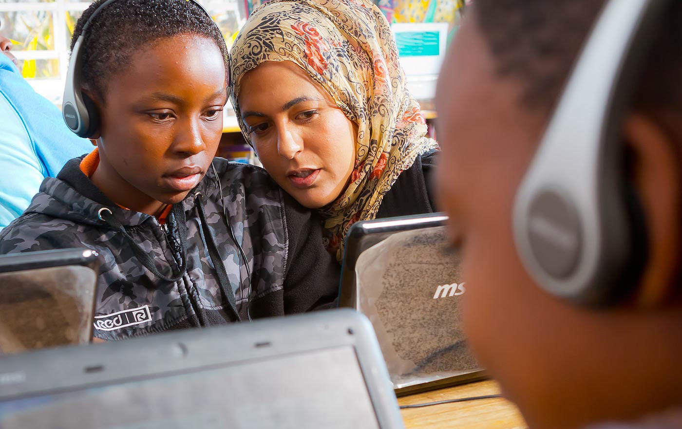 Educator instructs young student on laptops - Corporate social investment photography portfolio
