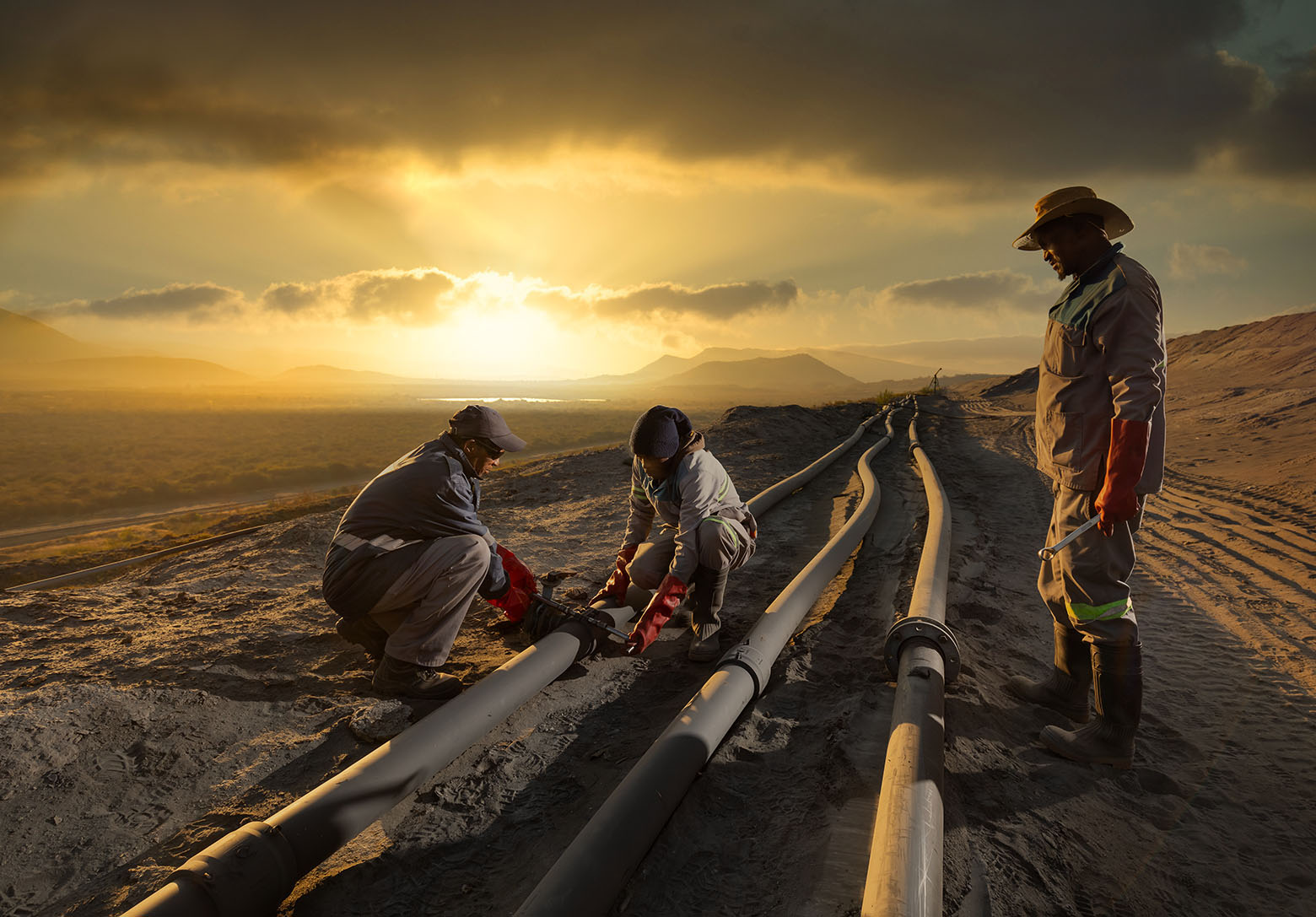 At work on pipework at sunrise on tailings dam