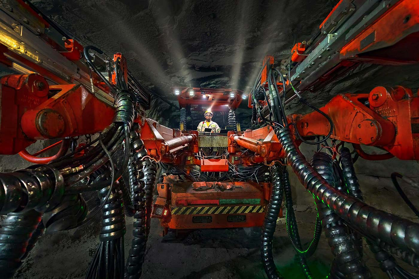 Twin boom trackless drill rig in action underground - mining machinery photography by Geoff Brown